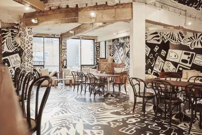 a private room with black and white mural artwork, long wooden tables and chairs and concrete pillars