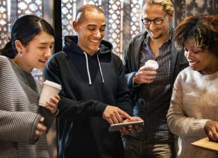 4 people stood with coffee looking at a phone