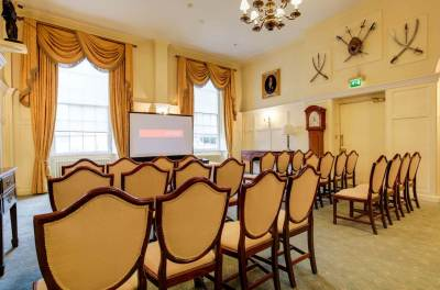 conference room with rows of chairs facing a projector, cream carpeting and curtains