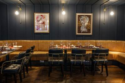private dining room with small wooden tables and boothed seating with art on the wall