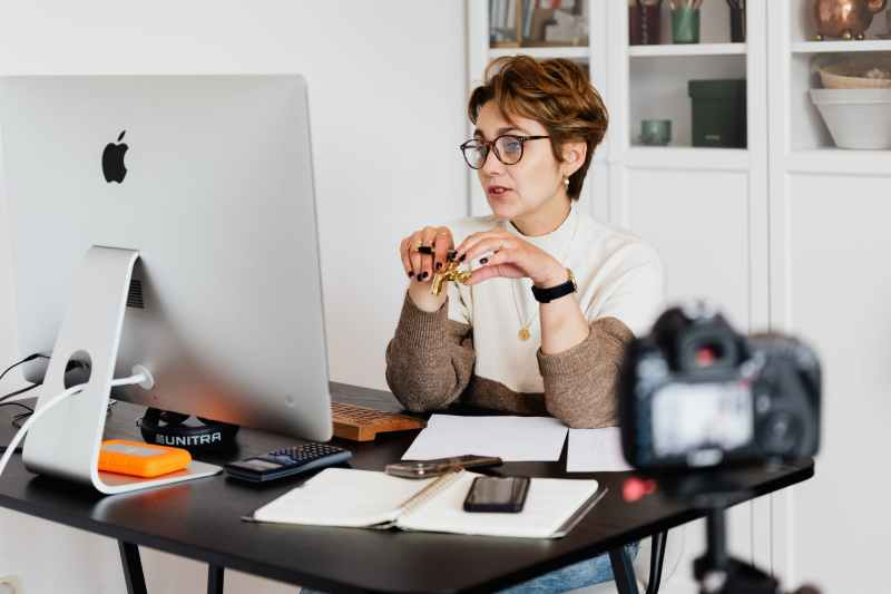 confident elegant lady in eyeglasses hosting webinar