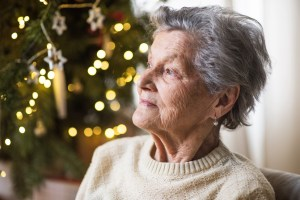 A portrait of a lonely senior woman in wheelchair at home at Christmas time.