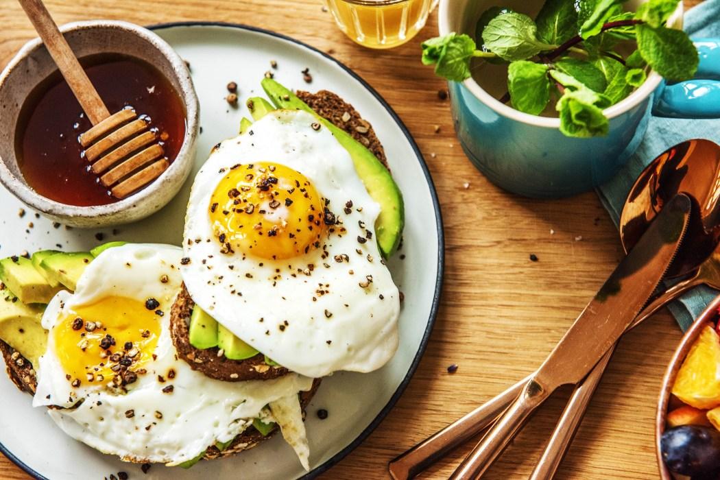 Frühstück im Bett: Eier und Avocado auf Brot