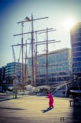 Asian Woman practicing Tai Chi in front of an old sailing ship