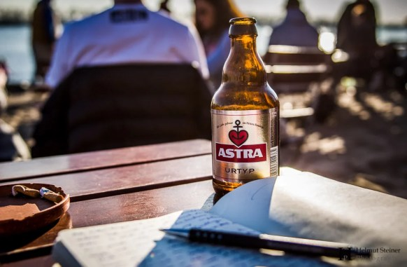 A moleskine travel journal with an ASTRA beer during sunset at Hamburg