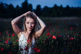 Portrait of a girl standing in a wild poppies field with a white summer dress