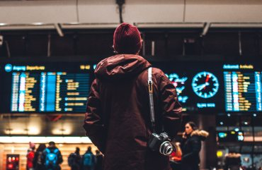 man staring at the flight board in airport