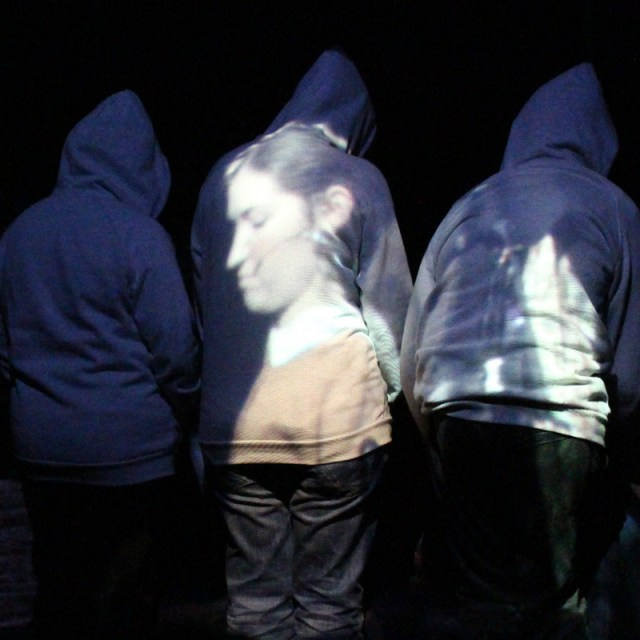 Three performers on stage. The performers are wearing grey hoodies and have their back to us. A live video of a fourth performer is projected on their backs
