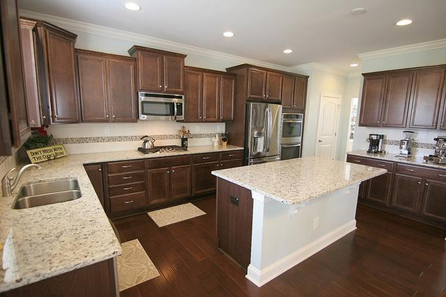 Large kitchen with granite countertops, stainless steel appliances, and a large counter island.