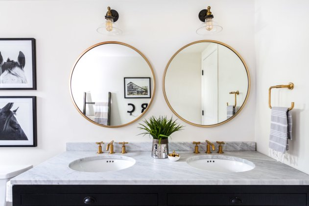 round mirrors and art in bathroom