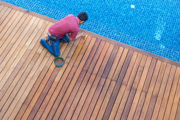 man staining deck