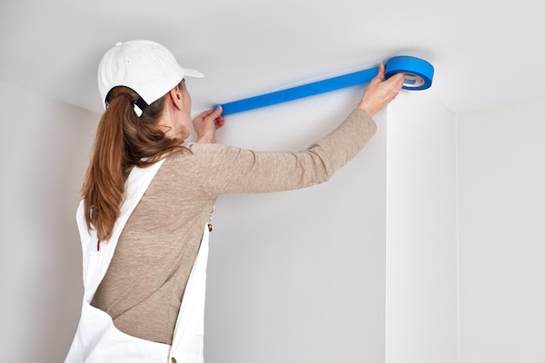 female interior painter taping the ceiling