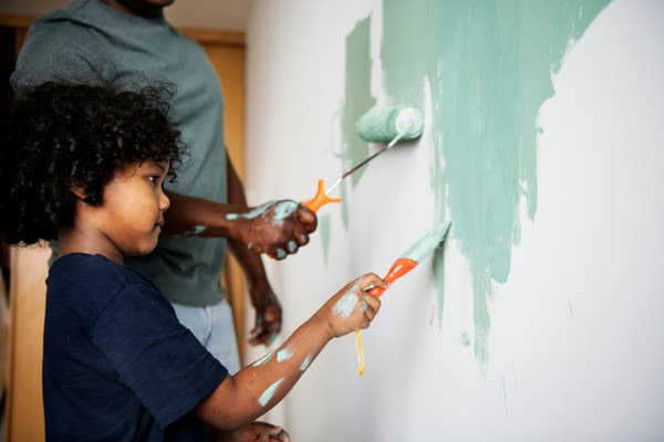 kid and parent painting wall