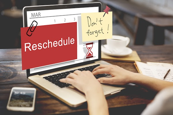 person at computer desk rescheduling appointment