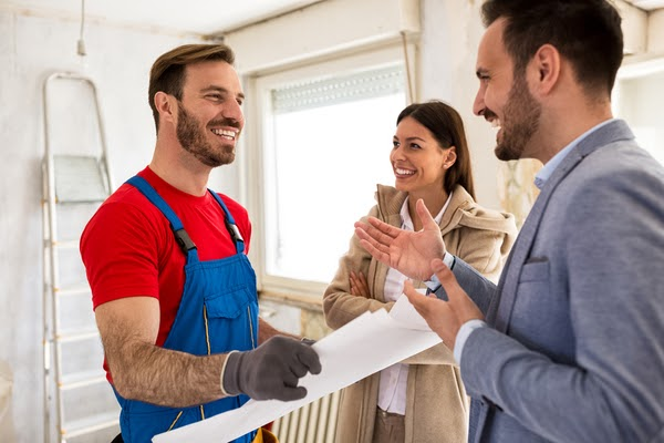 handyman going over plans with couple