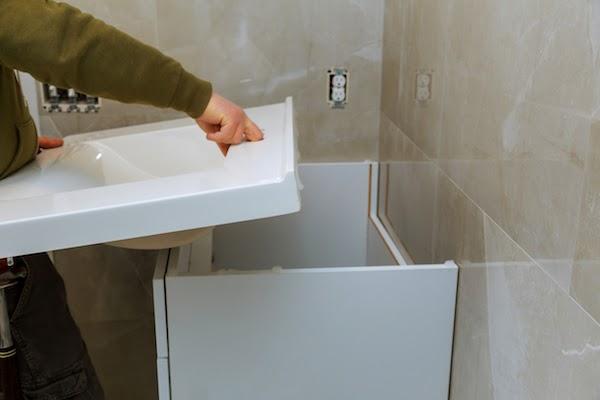 plumber installing vanity during bathroom renovation