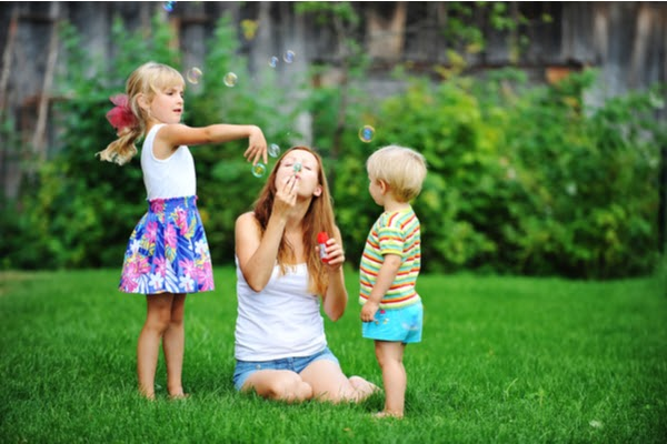 mother and two kids blowing bubbles on grass