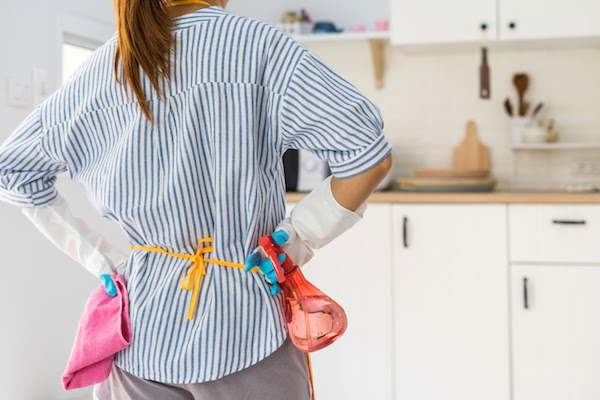 woman standing in kitchen about to spring clean cabinets