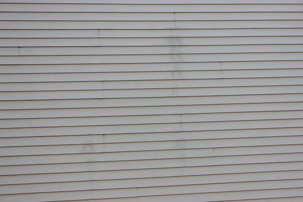 siding showing signs water stains and repairs needed