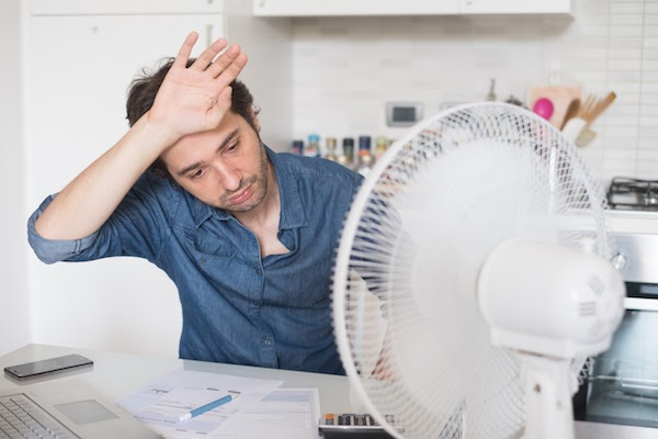 man hot in front of fan