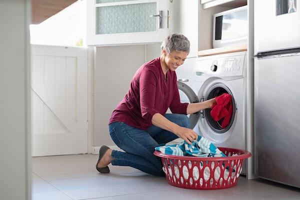 woman putting laundry into washing machine