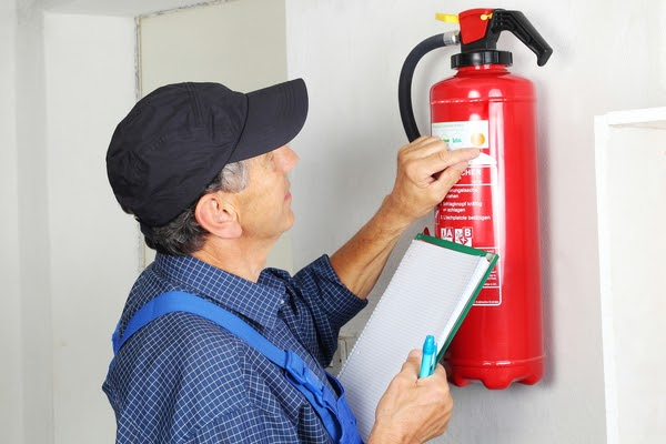 man checking expiry on fire extinguisher