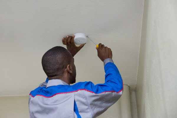 man installing smoke detector on ceiling
