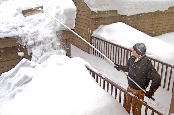 person clearing snow off roof during winter in canada