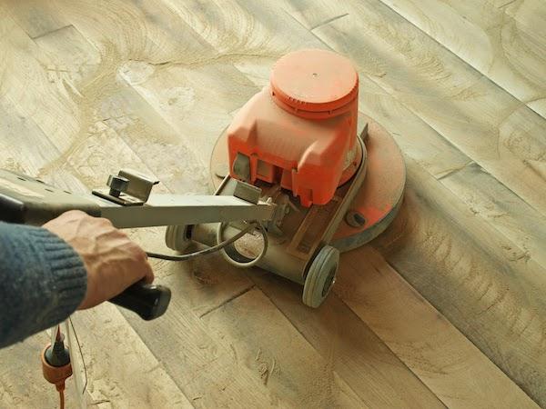 floor being sanded by worker