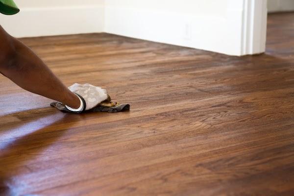 worker applying seal to refinished hardwood floors