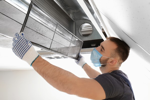 technician cleaning air duct