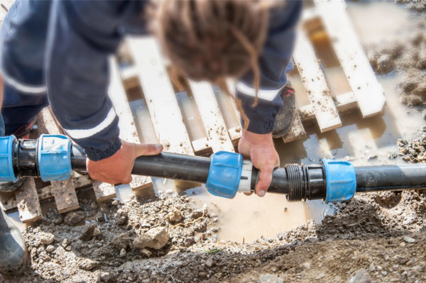 Plumber repairing broken pipe exterior on a muddy ground