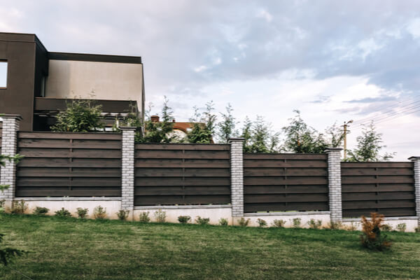 Horizontal tiered sections of brown wooden boards fence and white brick pillars. Live plantings. Green thuja bushes and lawn. Territory landscaping. Capital fencing. Hedge and wall on a country house.