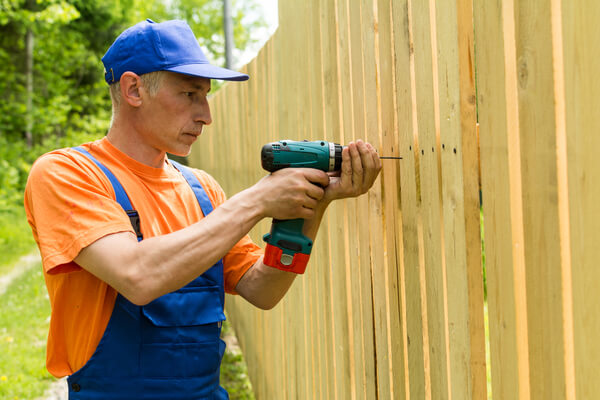 Carpenter twisting the screw in wooden board working at wooden fence outdoors
