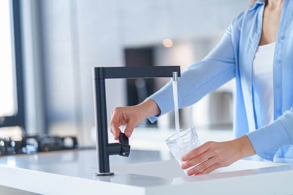 woman getting a glass of tap water