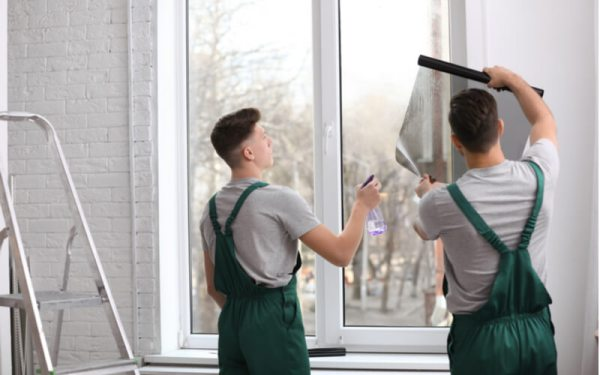 Professional workers tinting window with foil indoors