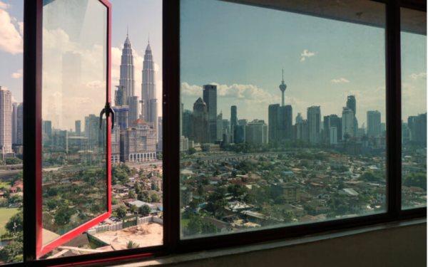 Transparent glass windows look like views of Kuala Lumpur city during sunny day
