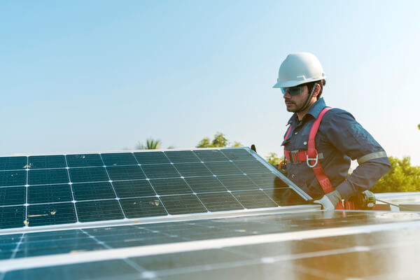 A technician installing the solar panels at roof top of home and home office ,concept of economic energy and cost saving ,own small business