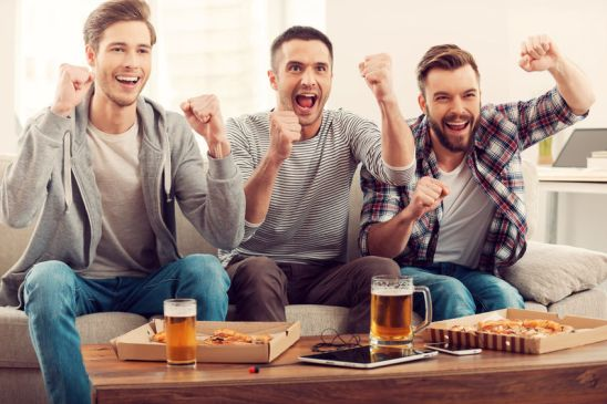 40227717 - domestic fans. three happy young men watching football game and keeping arms raised while sitting on sofa
