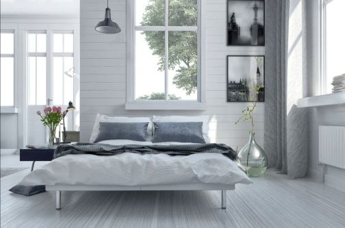 38436632 - double divan bed in a light spacious upmarket modern bedroom with large windows and artwork on the walls in grey and white decor