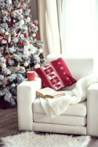 47181147 - opened book and a cup of tee on the cozy chair with warm blanket and cushion on it near christmas tree