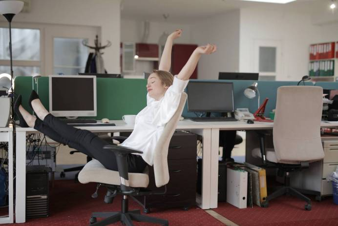 female office worker relaxing with feet on table