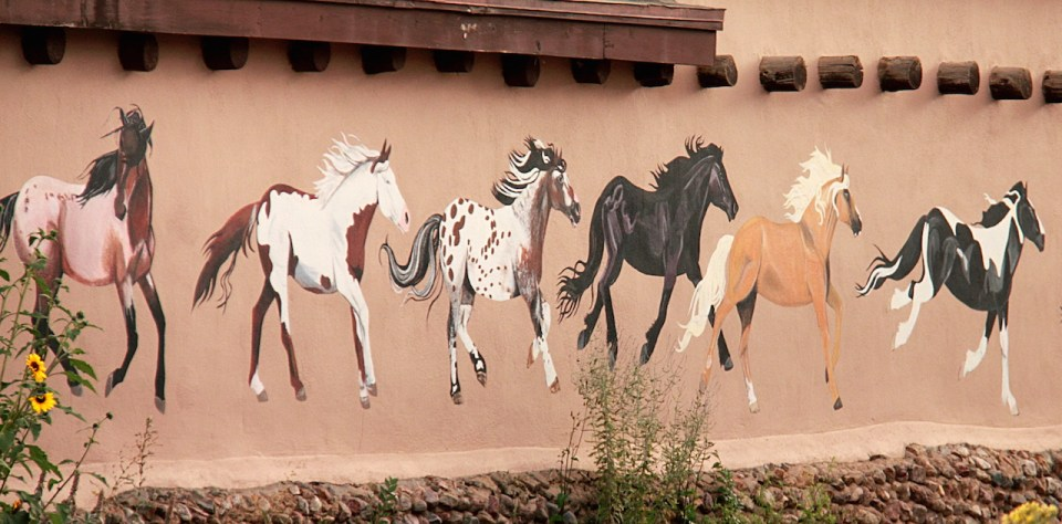 a Mural depicting wild painted horses on walls of old town in Taos, New Mexico