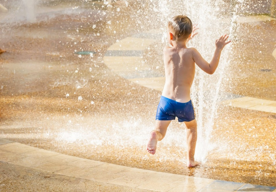 Cute happy child running through the water stream, or sprinkler, at a water park in the summer heat
