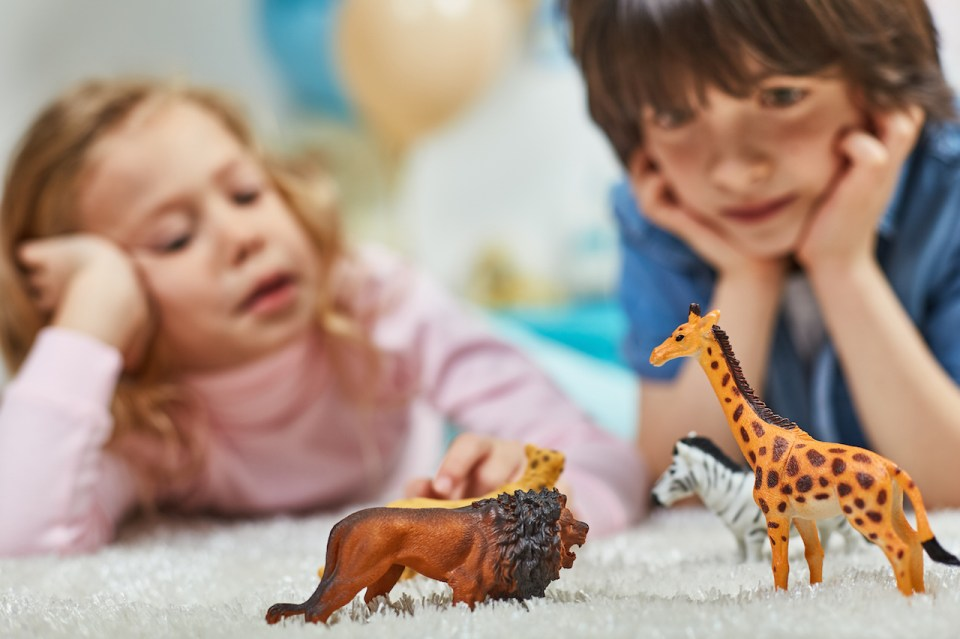 Young girl and young boy laying on the carpet playing with zoo animal figurines