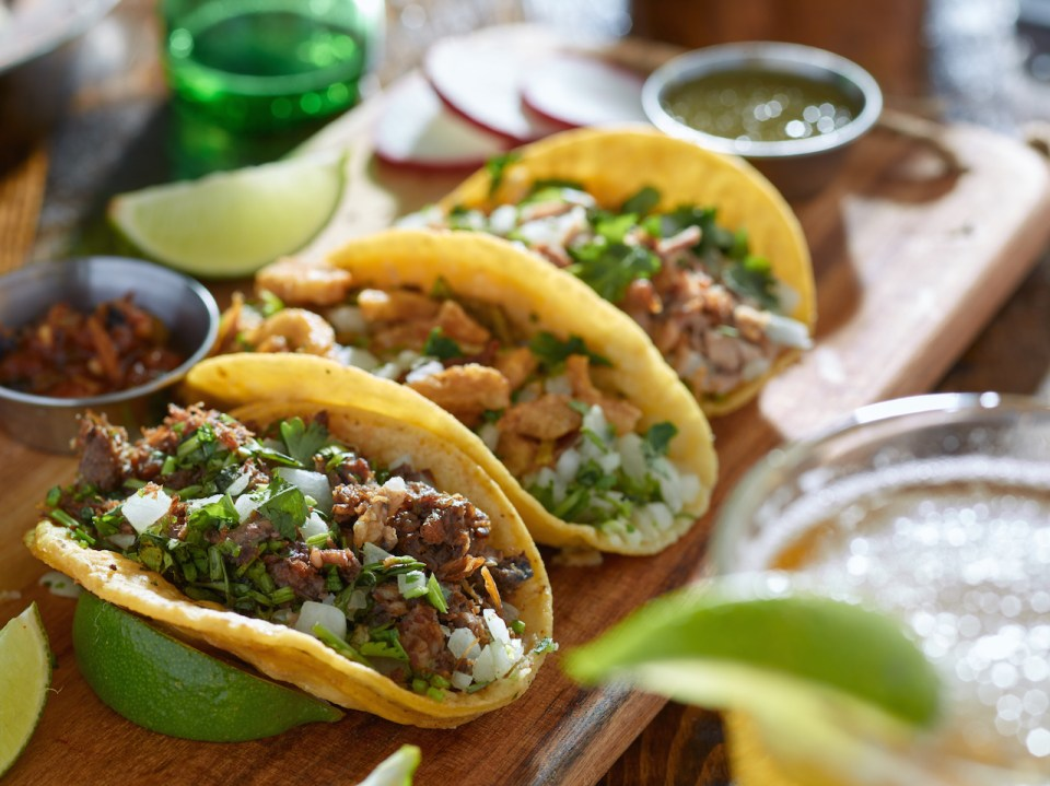 Plate of three mexican street tacos in yellow tortilla with beef and pork