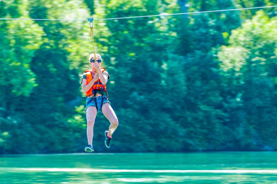 Young woman zipling over lake or river