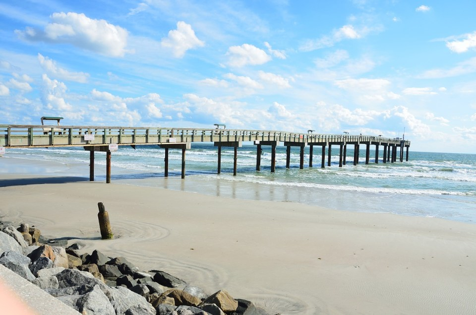 St. Augustine, Fl fishing pier. Clear water and bright blue skies with white clouds in the background