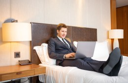 Working in hotel room. Confident young businessman in suit and tie working on laptop while sitting on the bed in hotel room