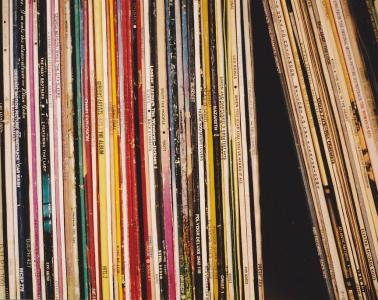 Old, classic vinyl records lined up on shelf.